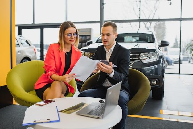 Biznes kobieta kupuje samochód w salonie samochodowym