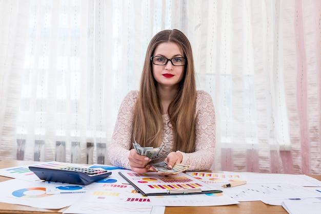 Biznes kobieta liczenia banknotów dolarowych w biurze
