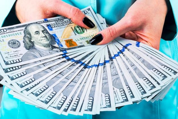 Biznes kobieta liczy pieniądze w ręce. garść pieniędzy. oferowanie pieniędzy. kobiece ręce trzymają pieniądze o nominałach 100 dolarów