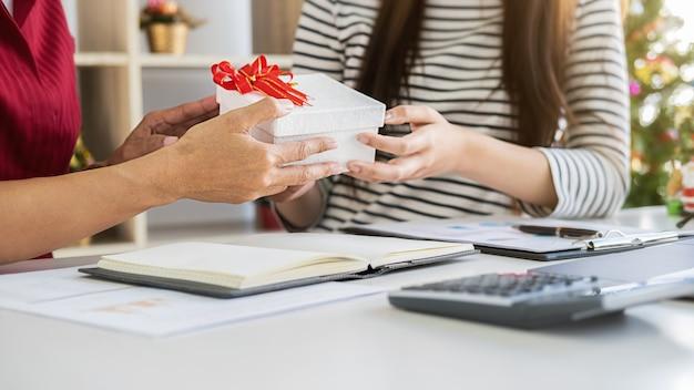 Biznes kobieta menedżer dając prezent swoim kolegom w ostatnim dniu roboczym. młodzi kreatywni ludzie świętują wakacje w nowoczesnym biurze.