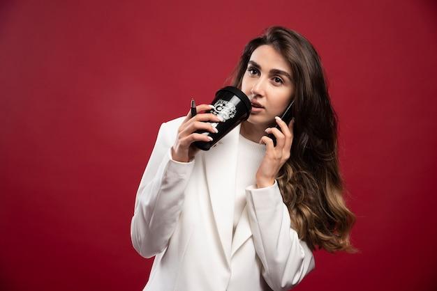 Biznes kobieta mówi przez telefon i pije z filiżanki kawy