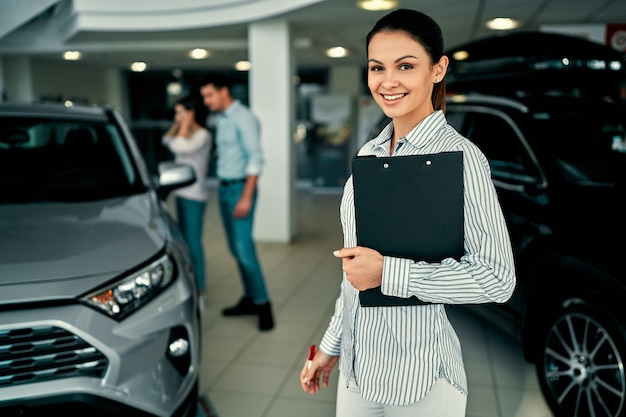 Biznes kobieta na salonie samochodowym i ludzie rozmyte tło.