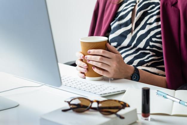 Biznes kobieta o filiżankę kawy przy biurku w minimalistycznym biurze. młoda osoba płci żeńskiej przed komputerem stacjonarnym w nowoczesnym miejscu pracy