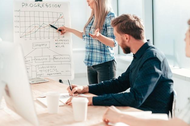 Biznes kobieta omawiając wyniki finansowe podczas spotkania roboczego z pracownikami