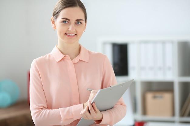 Biznes kobieta patrząc w kamerę trzyma folder w dłoniach i uśmiecha się