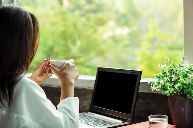 Biznes kobieta pije kawę w domowym biurze