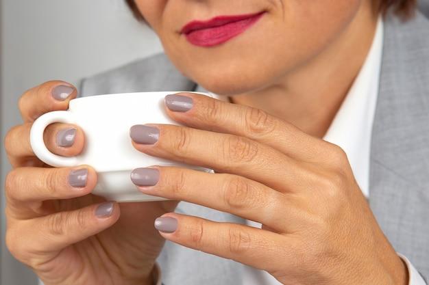 Biznes kobieta pije kawę z bliska biały kubek