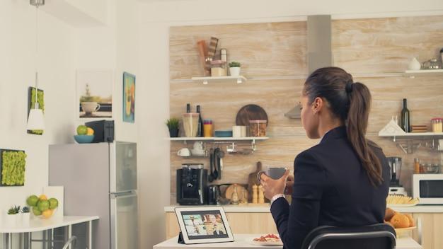 Biznes kobieta podczas rozmowy wideo z przyjaciółmi podczas jedzenia śniadania przed wyjściem do biura. korzystanie z nowoczesnej technologii internetowej online do czatowania za pośrednictwem aplikacji wideokonferencyjnej z kamerą internetową z krewnymi,