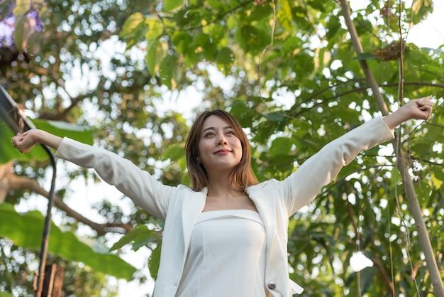 Biznes kobieta podniósł ramiona ze szczęścia i orzeźwiający w piękny dzień.