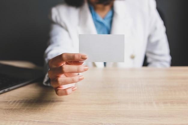 Biznes kobieta pokazując pustą białą wizytówkę lub wizytówkę w biurze tabeli