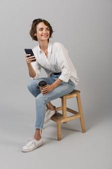 Biznes kobieta pozowanie na białym tle nad szarej ścianie, siedząc na stołku za pomocą laptopa na czacie przez telefon