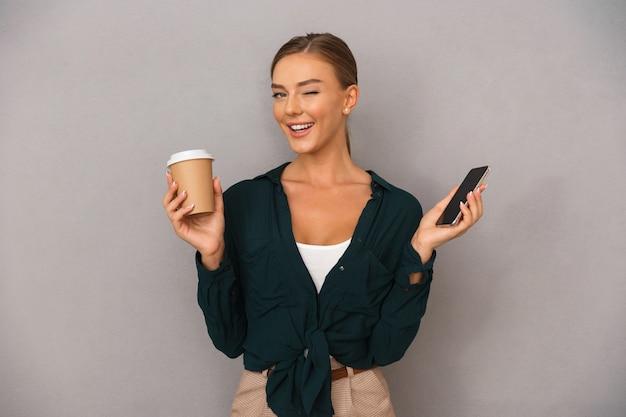 Biznes kobieta pozowanie na białym tle nad szarym tle ściany picia kawy przy użyciu telefonu komórkowego.