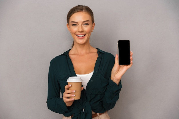 Biznes kobieta pozowanie na białym tle nad szarym tle ściany picia kawy wyświetlono wyświetlacz telefonu komórkowego.