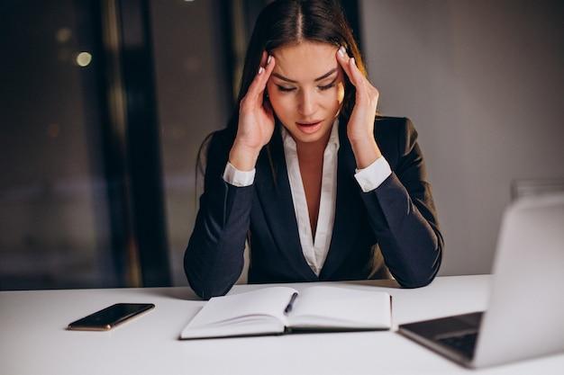 Biznes kobieta pracuje do późna w nocy na komputerze w biurze