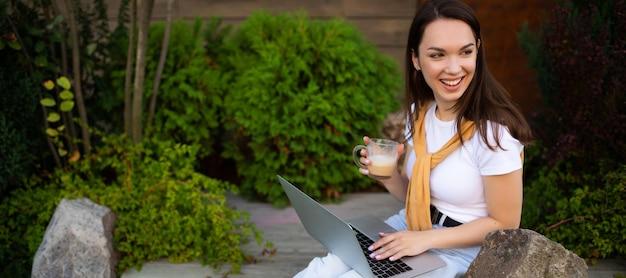 Biznes kobieta pracuje przy komputerze na ulicy.