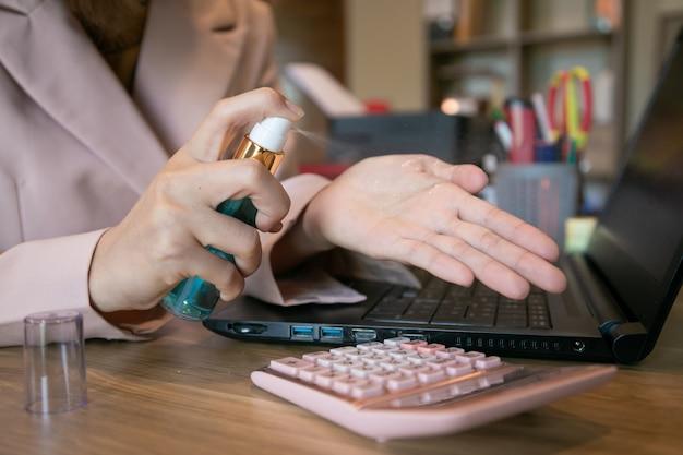 Biznes kobieta pracuje w domu, czyszczenie rąk żel antybakteryjny, aby wyeliminować zarazki. zostań w domu. dziewczyna uczy się, używając laptopa. wolny zawód. zapobiegaj wirusowi covid-19.