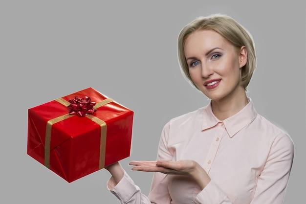 Biznes kobieta prezentuje pudełko. ładna kobieta pokazując pudełko stojący na szarym tle. zdobądź bonus wakacyjny.