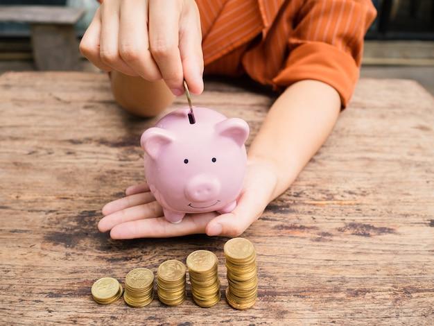 Biznes kobieta ręka oddanie monety do różowej skarbonki z wykresem wzrostu stosu złotych monet, oszczędzając pieniądze na przyszły plan inwestycyjny i koncepcję funduszu emerytalnego.