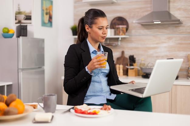 Biznes kobieta robi sobie przerwę i relaksuje się oglądając klip wideo, pijąc sok pomarańczowy