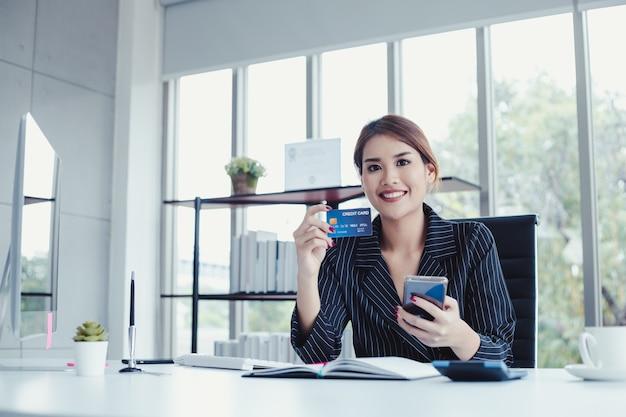 Biznes kobieta robi zakupy online przez telefon komórkowy za pomocą kart kredytowych, płacić rachunki.