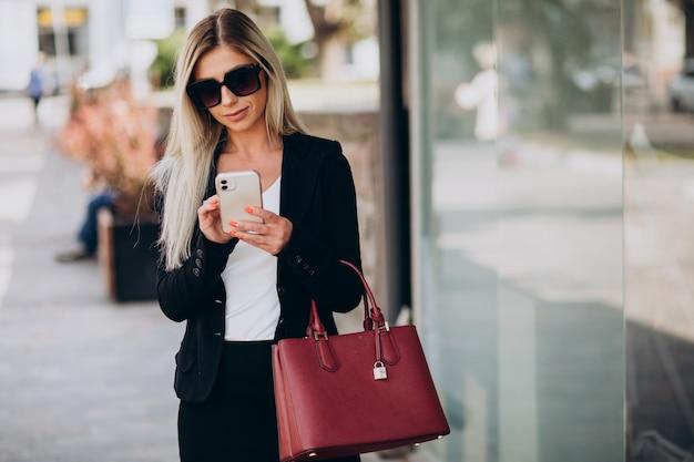 Biznes kobieta rozmawia przez telefon na ulicy