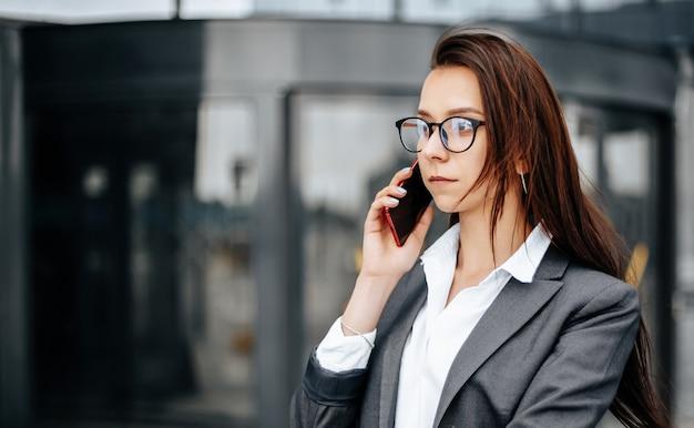 Biznes kobieta rozmawia przez telefon w mieście w dniu roboczym, czekając na spotkanie.
