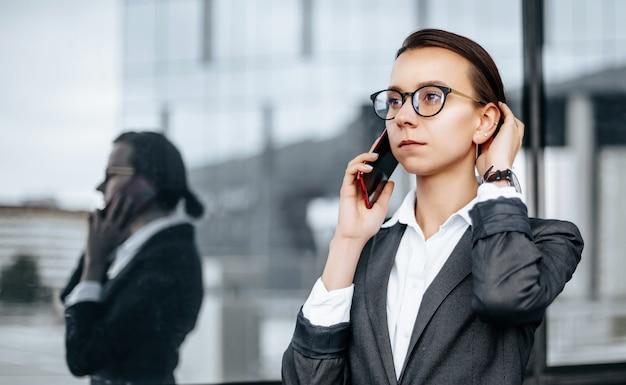 Biznes kobieta rozmawia przez telefon w mieście w dzień roboczy, czekając na spotkanie