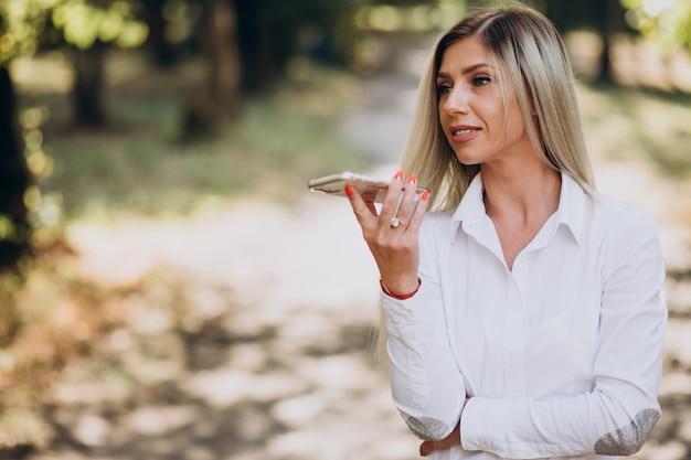 Biznes kobieta rozmawia przez telefon w parku