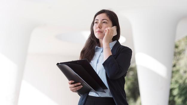 Biznes kobieta rozmawia telefon niski kąt