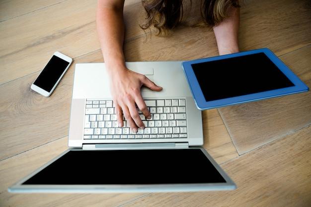 Biznes kobieta siedzi na ziemi na laptopie i tablecie