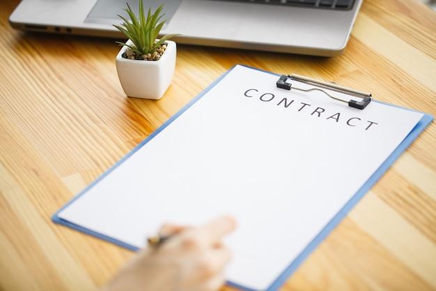 Biznes kobieta siedzi przy biurku podpisanie umowy z płytkie skupić się na podpisie.