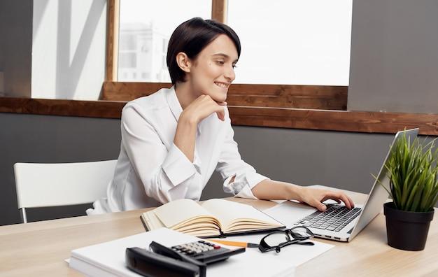 Biznes kobieta siedzi przy stole roboczym przed biurem finansów laptopa