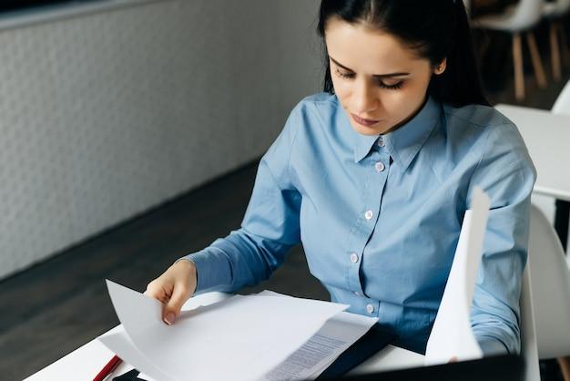 Biznes kobieta siedzi w biurze przy stole i bada dokumenty