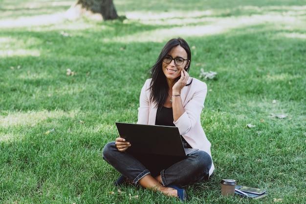 Biznes kobieta siedzi w lato trawa park za pomocą laptopa.