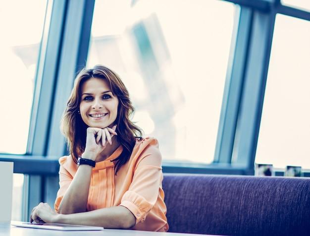 Biznes kobieta siedzi za biurkiem w przestronnym biurze. zdjęcie ma puste miejsce na twój tekst