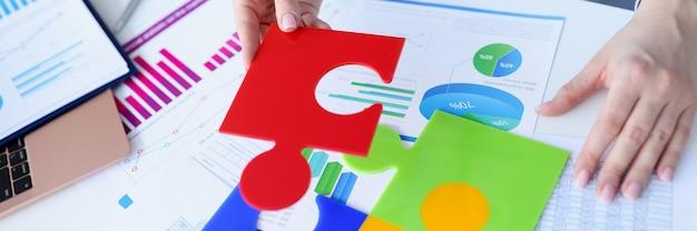 Biznes kobieta składane kolorowe puzzle nad zbliżeniem dokumentów.