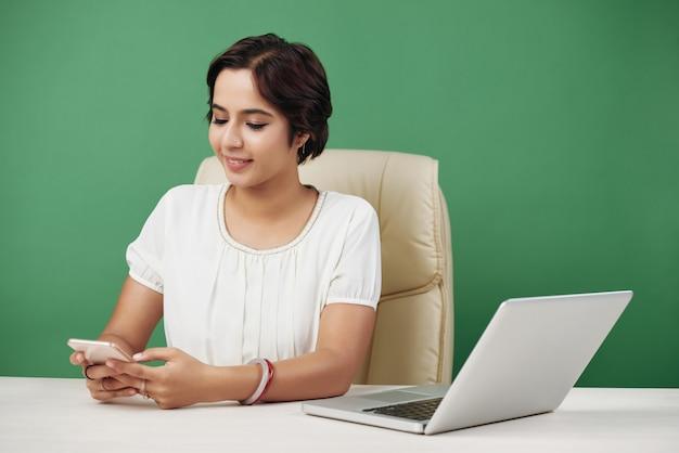 Biznes kobieta sms-y z przyjaciółmi lub kolegami