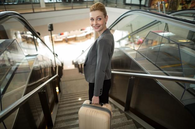 Biznes kobieta stojąc na schodach ruchomych z bagażem