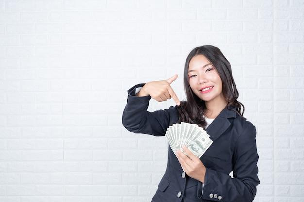 Biznes kobieta trzyma banknot, gotówka oddzielnie, biały mur ceglany wykonane gesty z języka migowego.
