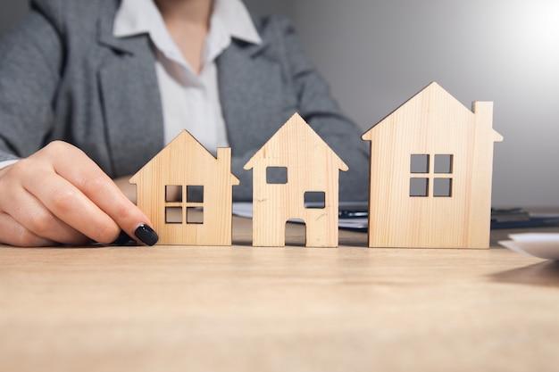 Biznes kobieta trzyma drewniane modele domów.