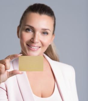 Biznes kobieta trzyma kartę kredytową przed jej twarz na białym tle portret studyjny