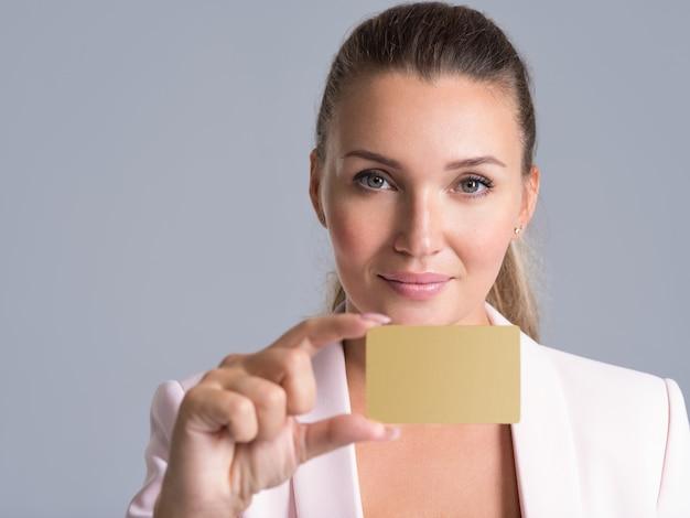 Biznes kobieta trzyma kartę kredytową przed jej usta na białym tle portret studyjny