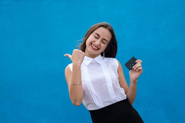 Biznes kobieta trzyma kluczyki do samochodu na białym tle na niebieskiej ścianie. sprzedaż