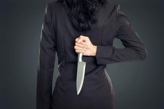 Biznes kobieta trzyma nóż za jego plecami