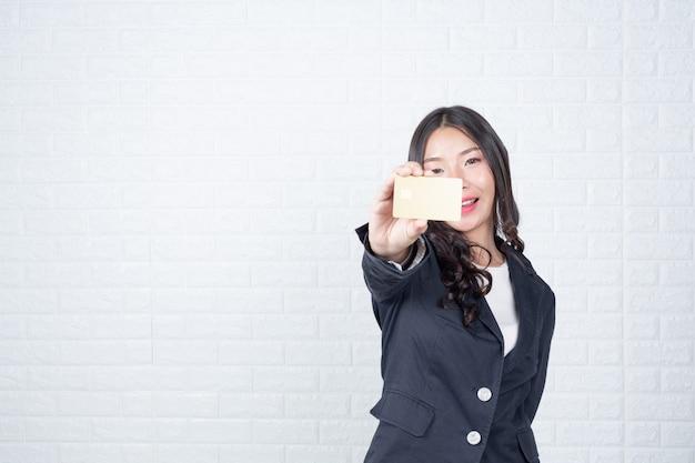 Biznes kobieta trzyma oddzielną kartę gotówkową, biały mur ceglany wykonane gesty z języka migowego.