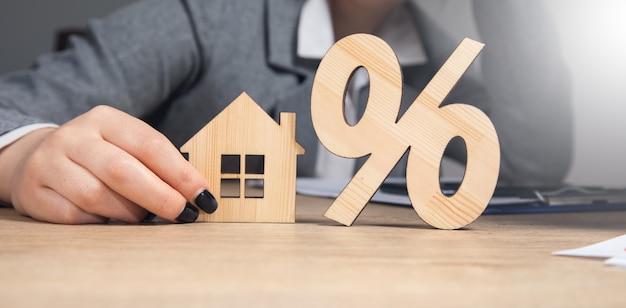 Biznes kobieta trzyma procent z modelem domu.