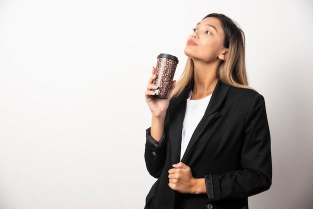 Biznes kobieta trzymając kubek i pozowanie na białej ścianie.