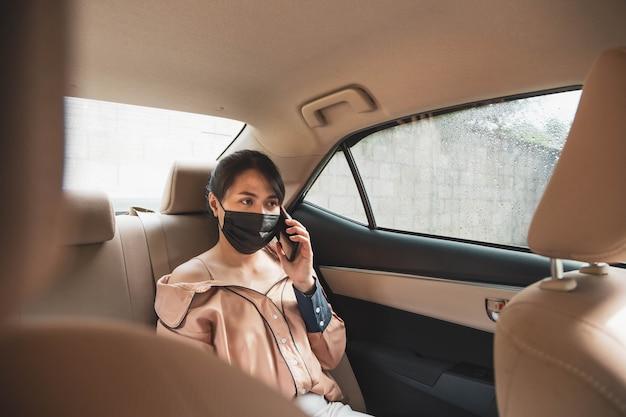 Biznes kobieta ubrana w ochronną maskę na twarz rozmawia przez telefon komórkowy, siedząc na tylnym siedzeniu w samochodzie