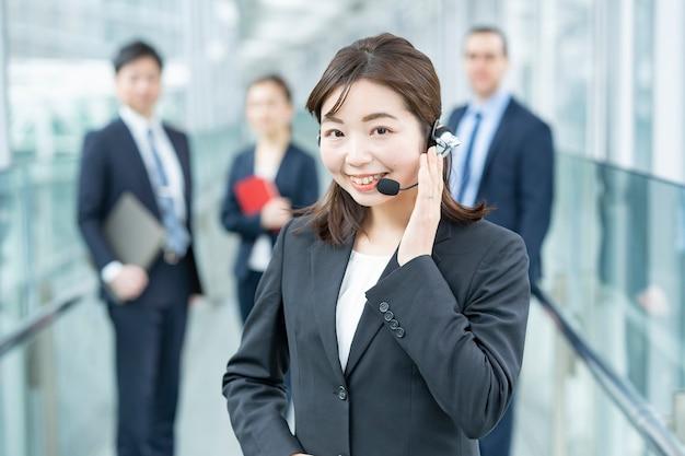 Biznes kobieta ubrana w zestaw słuchawkowy i jej zespół biznesowy