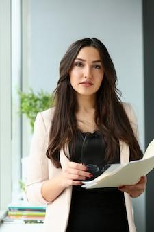 Biznes kobieta w beżowym garniturze, trzymając dokumenty